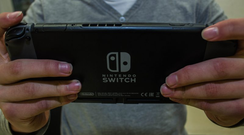 Spieler spielt auf der Nintendo Switch. Die Rückseite wird gezeigt, dort ist das Logo zu sehen.